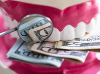 Dental model with money between teeth