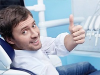 Smiling man in dental chair giving thumps up