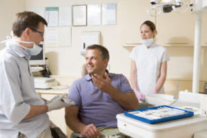 Man talking to dentist in dental exam room